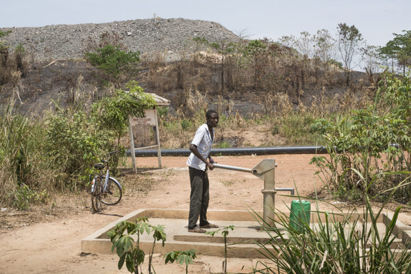 Silvia Savato drawing water from a pump in the community of Anane Krom. In the background the mountain of stones result of mining activity is observed.