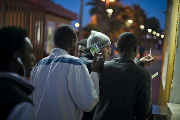 Migrants passing through the gate of the CETI immigrantion centre in Melilla