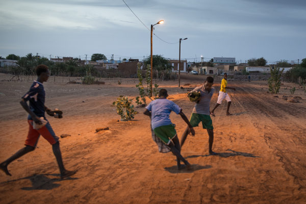 group of children playing football at sunset in Oued area of Chinguetti.