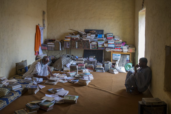 Hammed Ahmed Mohamed Cheikh, imam of the mosque of Ouadane, leafing through one of his manuscripts under the watchful eye of Barakala, local guide. Coexist in this library volumes from the Middle Ages to modern books in apparent disorder. For centuries, the Koranic school children have used this collection to learn Arabic and the basics of their religion.